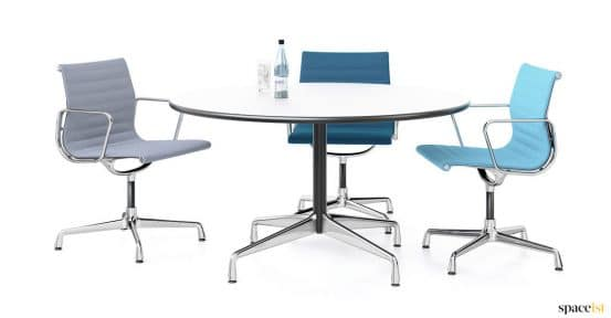 Three blue chairs around a round whit table