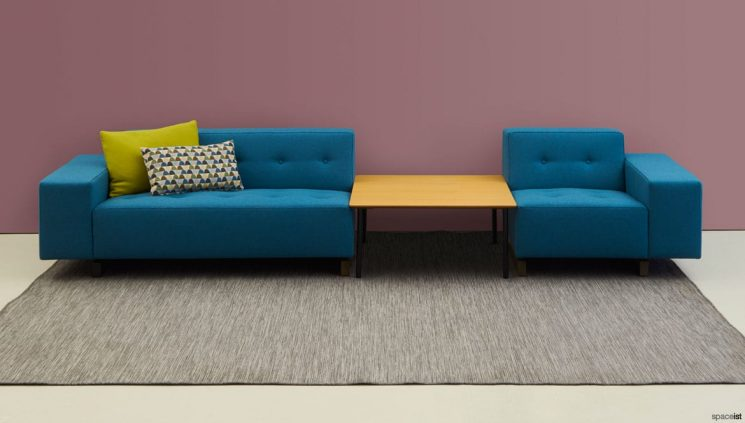 Long Blue Sofa that is split in the middle with a Coffee Table