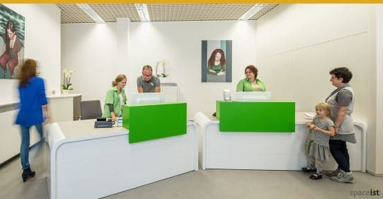 Hi-line white clinic reception desk with a green screen