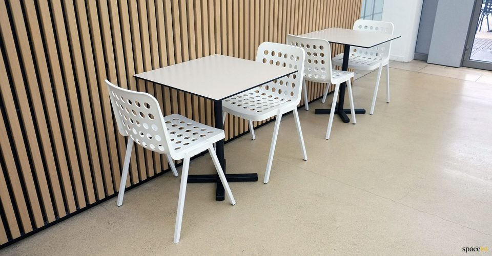 White cafe chairs with holes in seat