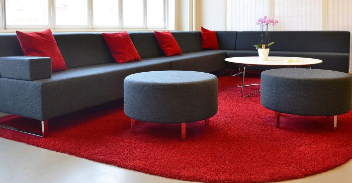 Large grey corner office sofa with red cushions