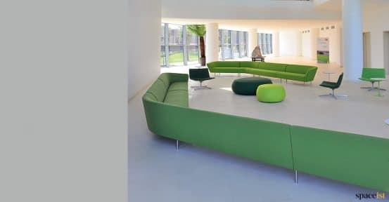 Long green sofa angled in modern room