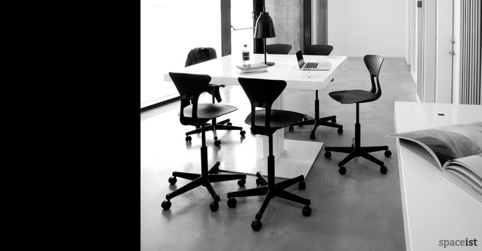 Milk standing desk with high black stools