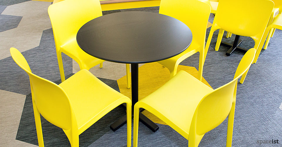 bold black tables with yellow cafe chairs